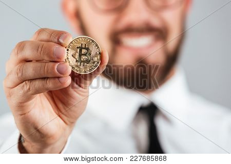 Close up of a smiling man showing golden bitcoin isolated over gray background