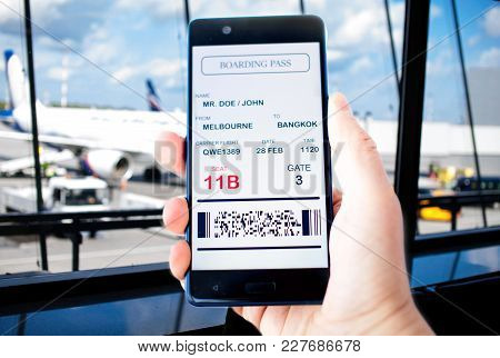 Electronic Boarding Pass On The Screen Of Smartphone. Concept Of Modern Travel. Boarding Pass Is Fak