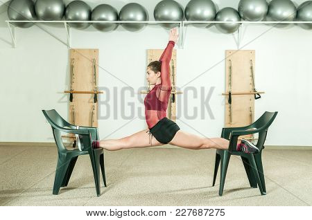 Young Attractive Fitness Girl Workout Leg Split On Two Chairs As Preparation For Gymnastic Competiti