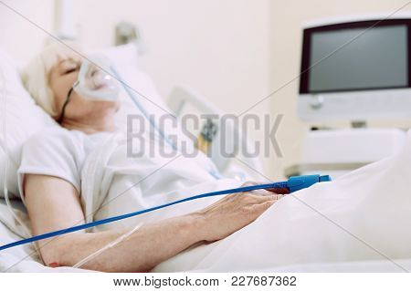 Fragile Heart. Selective Focus On A Hand Of A Poor Woman Lying In A Hospital Bed With A Heart Rate M