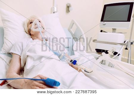 Difficult Breathing. Tired Elderly Lady Wearing An Oxygen Mask Lying In A Hospital Bed With A Heart
