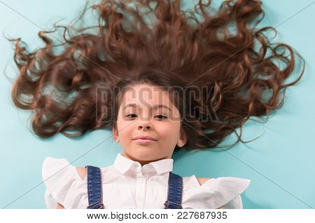 Girl With Long Healthy Brunette Hair On Blue Background. Little Child With Curly Hairstyle, Curls. B