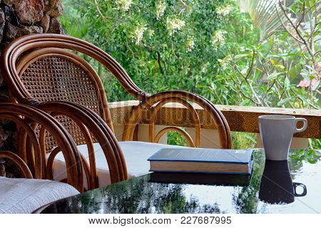 Wicker Chair On Balcony, Cup Of Coffee And Book. Concept Calmness, Meditation, Old Age, Downshifting