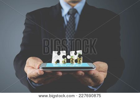 Hand Of Businessman Holding Smart Phone Blue Touchscreen. Hand With Jigsaw Of Coin. Businessman Hand