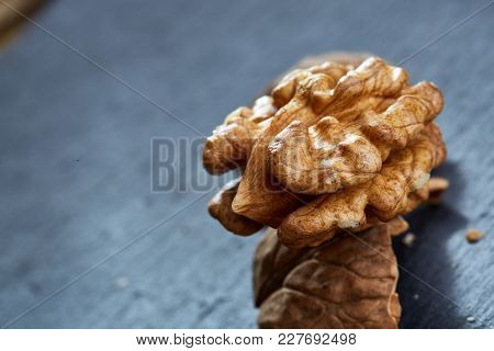 Top View Close-up Picture Of Nutritious Tasty Dry Cracked Walnuts On Dark Background, Shallow Depth