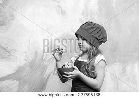 Cookies Or Biscuits In Bowl In Hand Of Chef Kid Or Small Girl In Cook Hat And Apron With Distaste On