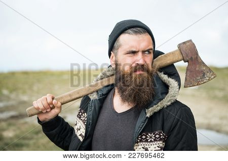 Lumberjack In The Woods With An Ax. Brutal Bearded Man With Beard And Moustache On Winter Day, Snowy