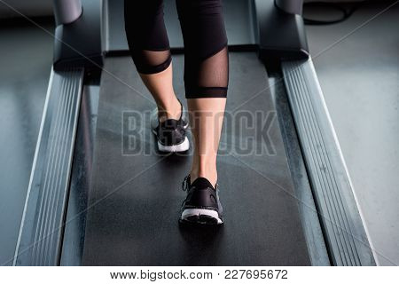 Close Up Female Muscular Feet In Sneakers Running On Treadmill At Fitness Gym