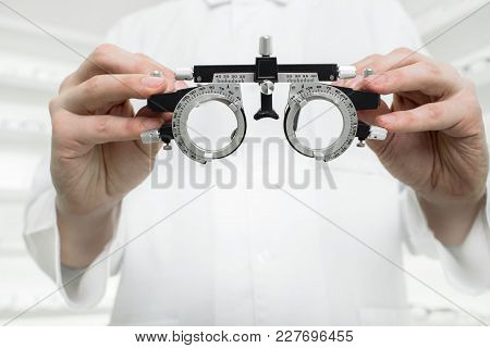 Doctor Hands Holding Optometrist Ophthalmological Device For Vision Testing. Checking Vision Concept