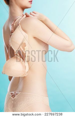 Bosom Concept. Slim Attractive Naked Woman Holding Beige Plunge Bra In Hand, On Blue