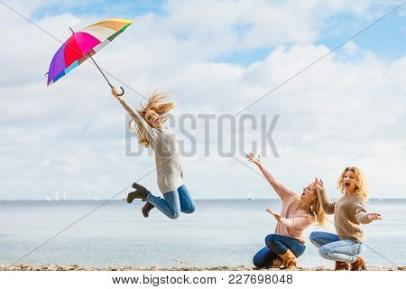 Three Women Full Of Joy Jumping Around With Colorful Umbrella. Female Friends Having Fun Outdoor.