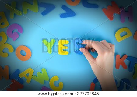 The Girl Puts Out Of The Multicolored Letters The Words Yes. Beautiful Unusual Background With Vigne