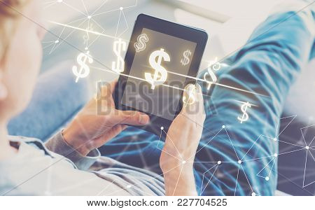 Dollars With Man Using A Tablet In A Chair