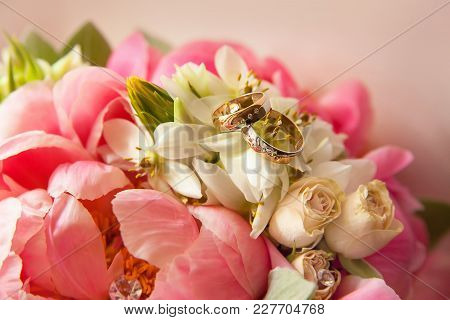 Two Gold Wedding Rings Lie On A Bouquet Of Flowers, Close-up