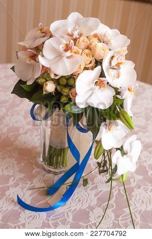 Two Gold Engagement Rings Lie On A Bouquet Of Flowers, Glass Vase On A Table With A Wedding Bouquet