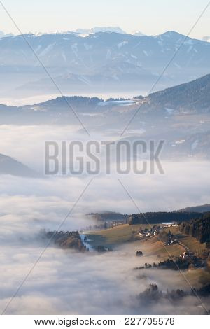 Hill Looking Through Low Stratus Fog With Mountain Range Hochschwab In The Background