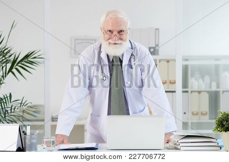Happy Senior General Practitioner At His Table