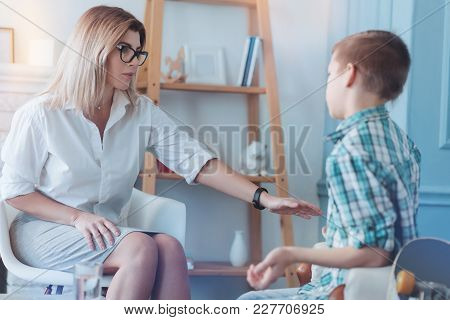 Do Not Worry Honey. Female Psychotherapist Reaching Out To A Male Youngster While Both Chatting Over