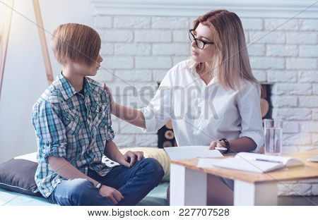 You Can Trust Me. Careful Psychology Professional Putting Her Hand On A Shoulder Of A Young Patient