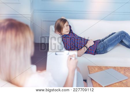 Teenage Problems. Male Youngster In Casual Attire Relaxing On A Sofa And Looking At A Professional D