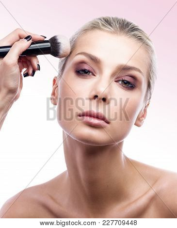 The Work Of A Professional Makeup Artist. The Beautiful Young Woman's Face And Brush The Powder In C