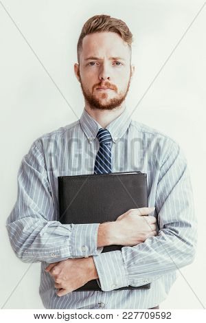 Closeup Portrait Of Serious Young Business Man Looking At Camera And Holding Folder. Isolated Front