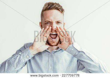 Closeup Portrait Of Serious Young Man Looking At Camera, Opening Mouth Widely, Cupping Hands Around