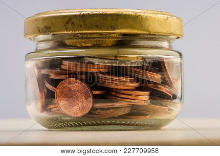 Group Of Coins And Euro Banknotes In A Glass Jar. Euro Money. Blurred Background.