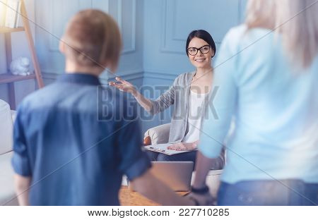 Please Sit Here. Young Professional Wearing Glasses Looking At A Family Standing In Front And Welcom
