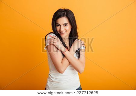 Image of cute cheerful young woman standing isolated over yellow background wall. Looking camera.