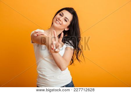 Photo of amazing pretty young woman standing isolated over yellow background wall showing peace gesture. Looking camera.