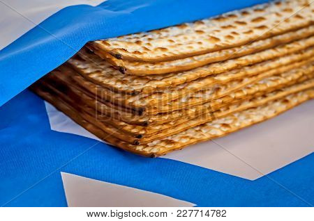 A Pile Of Traditional Jewish Passover Matzah Unleavened Bread Wrapped In The Flag Of Israel. Pesach