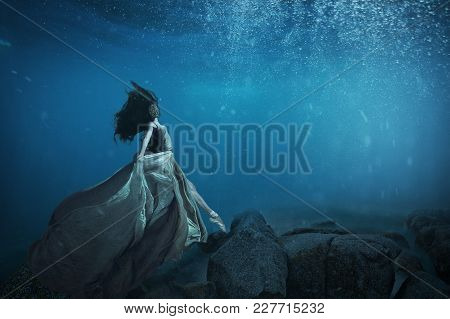 A Girl In Pointe Shoes And A Long Dress Is Walking On The Bottom Of The Ocean
