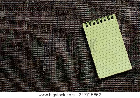 Shooters Notepad With Water Resist Paper Lies On Multicam Pattern Backgroun.
