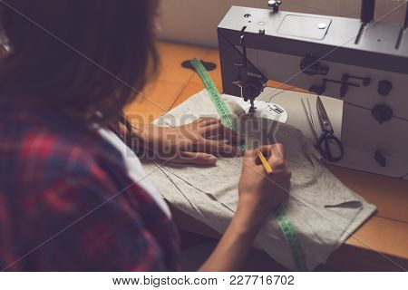 Young Seamstress Measuring The Length Of A Sweatshirt With A Measuring Tape And Marking It. Selectiv