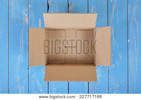 Postage And Packing Service - Open Package Top View On A Blue Wood Background.