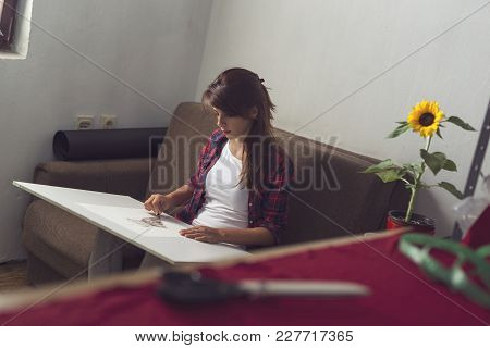 Young Fashion Designer Making A Sketch Of A New Dress Design