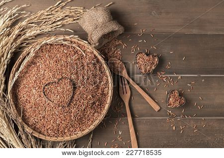 Various Rice:  Rice Berry, Brown And Thai Red Mixed Rice With Blank Notebook On Brown Wooden Backgro