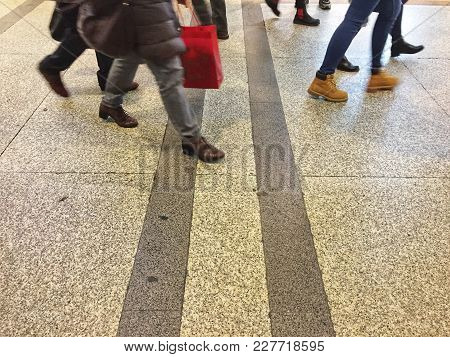 Feet Of People Walking On A Striped Street In The City