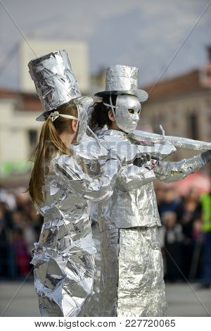 Unrecognizable Man Wrapped With Aluminium Foil, Violin Players