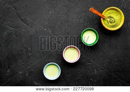 Brew Matcha Tea. Bowl With Powder And Cups With Beverage On Black Background Top View.