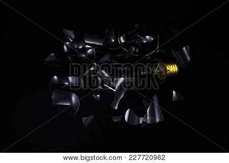 Broken Light Bulb On Dark Surface With Pieces Backlit