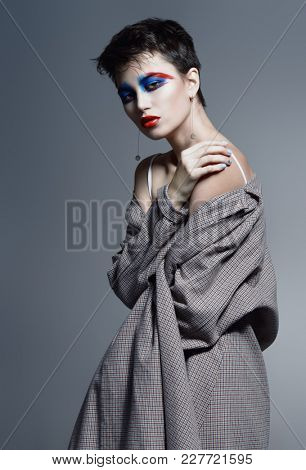 Female beauty, fashion. Attractive female model posing in stylish clothes over gray background. Studio shot.