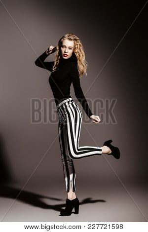 Attractive fashionable young woman wearing in striped trousers and boots. Youth style. Studio shot.