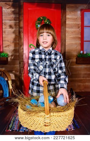 Happy little boy with basket full of painted eggs is standing on the porch near the wooden house. Easter holiday. Rural style, easter decoration.