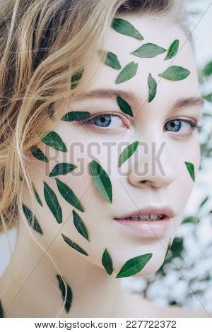 Beautiful young woman with green leaves on her face over white background. Cosmetics and makeup.