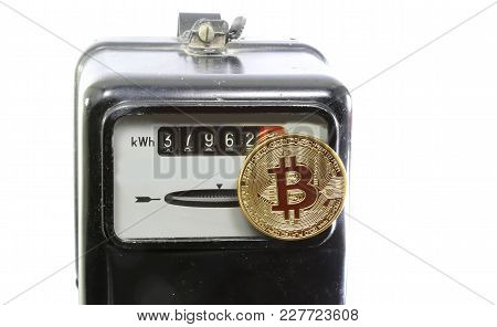 Big Golden Bitcoin Coin Over An Old Analog Electric Power Meter