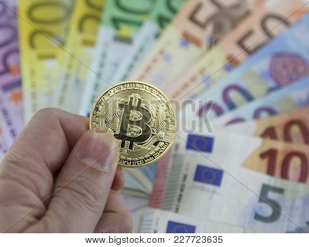 Hand With One Big Goden Bitcoin And Euro  On Background