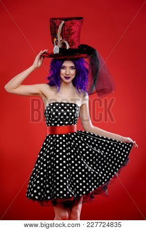 Beautiful girl with purple hair in a polka-dot dress and a huge hat posing on a red background. Beauty, fashion. Pin-up style.