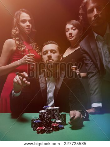 Emotional man in suit sitting at poker table and gesturing